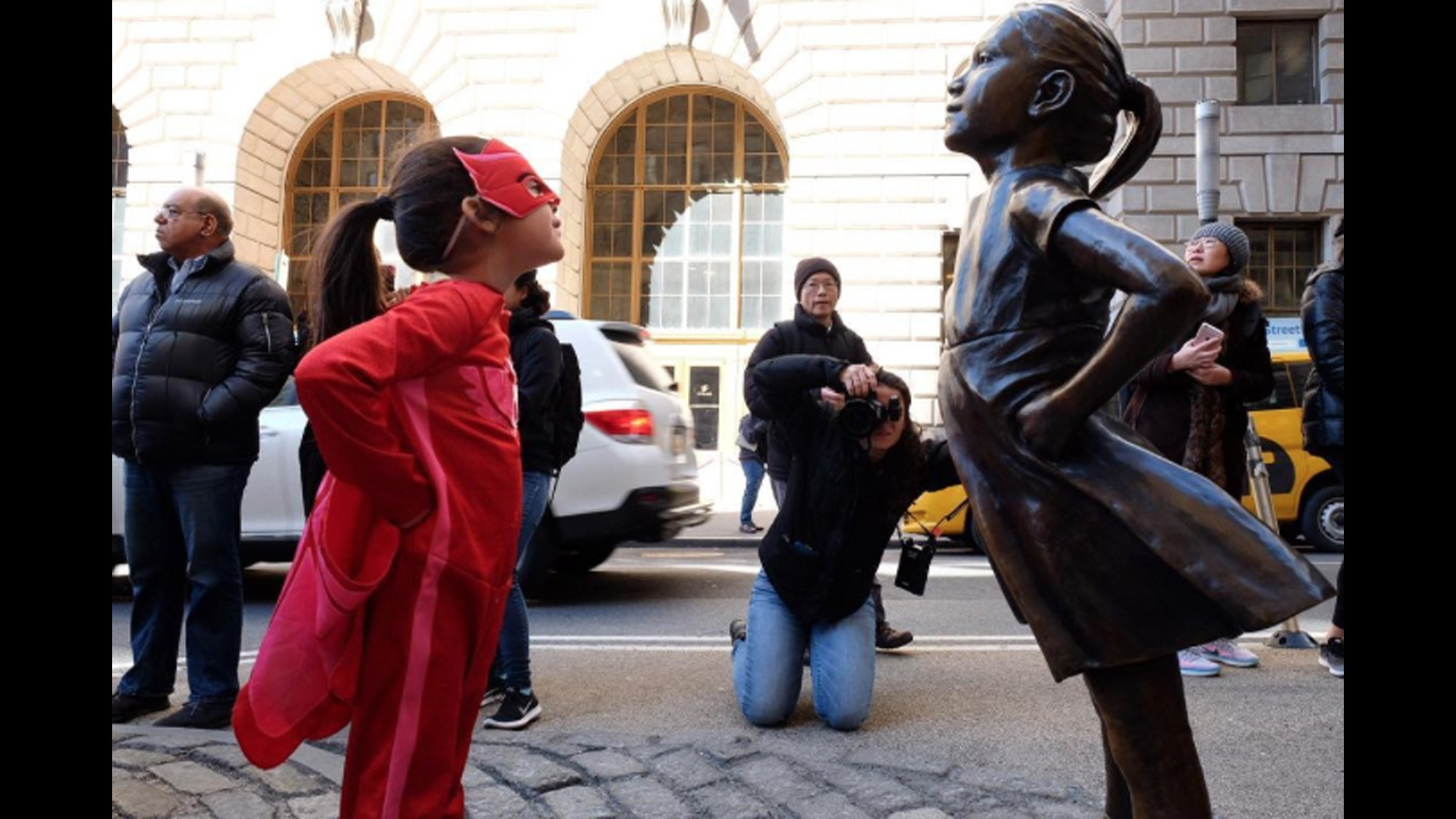 """Abrianna Tabor Almonte wears her red-and-pink superhero outfit to go see the """"Fearless Girl"""" statue on Wall Street."""
